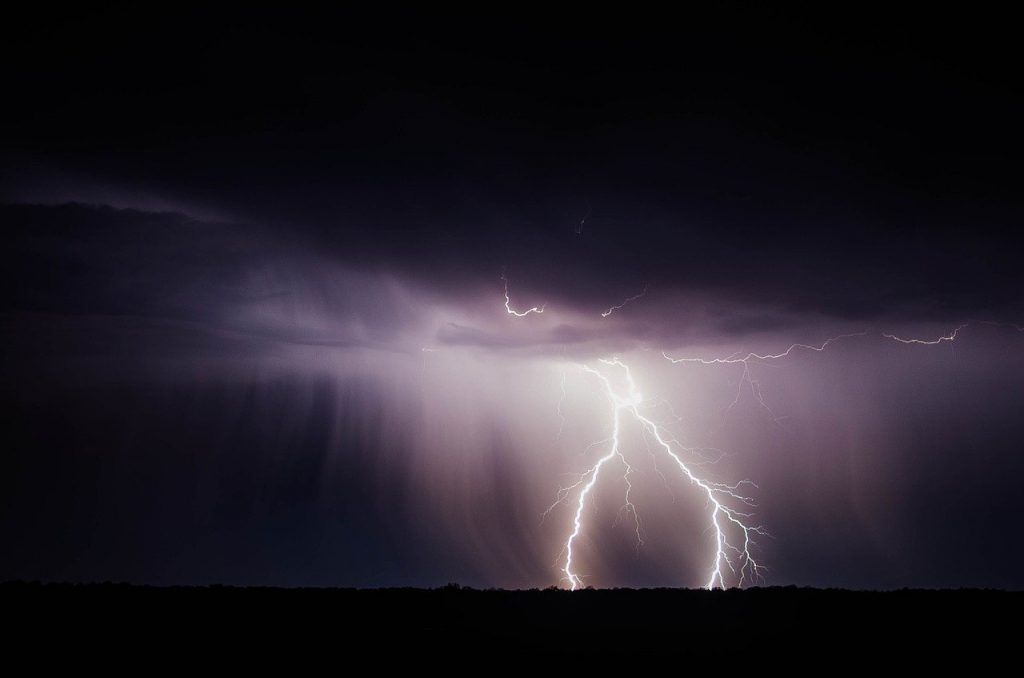Storm at night with lightning damaging roof
